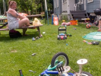 Kathy Case watches her nephew Donald Boyce lll on Wednesday in her Maple Avenue yard. Case said that the child's bicycle in the foreground has been stolen once but was found at the end of the street. Case said all the toys are now locked up at night.