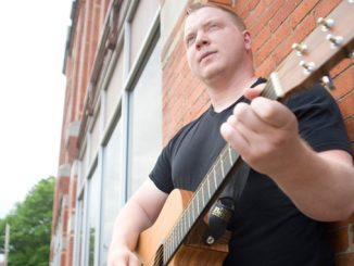 "Dana Twigg stands with his acoustic guitar Tuesday outside the Cortland Standard building in Cortland. The local musician has released his third album. ""Better View,"" seen below. On the cover is his grandfather."