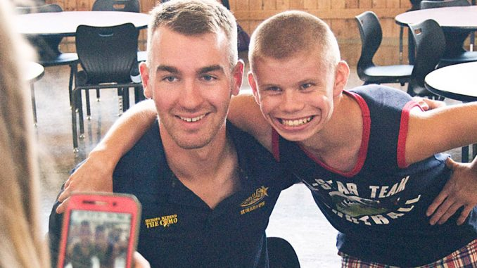 OCM-BOCES student Tyler Vieou has his photo taken with race car driver Cody Ware during Ware's visit to the school Wednesday afternoon. Ware will be driving his Camaro in the Xfinity Series at the Watkins Glen International race track on Saturday.