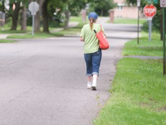 A woman walks along the side of Elm Street in Dryden, another street targeted for the addition of a sidewalk