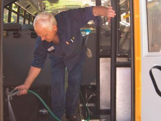 McGraw School District bus driver Chuck Lacey hoses out a bus Monday at the bus garage as he prepares for the first day of school on Sept. 7.