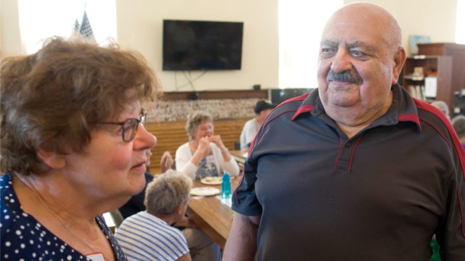JoAnn Dukelow, coordinator for the English as a Second Language program, left, talks with Russian speaking Lev Livshits, right, on Wednesday during a Literacy Day celebration at the Cortland Community Center.