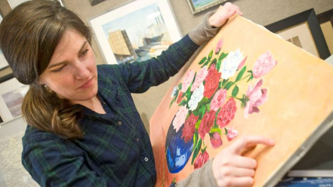 Emily Gibbons, director of the Cultural Council of Cortland County, will be staying in Cortland through the fall. In this file photo, she restores a damaged 47-year-old oil painting.