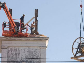 Eric Fuller, left, and Dan Torrance, of Woodford Brothers, look on as a bell is removed from the steeple of the Unitarian Universalist Church at 3 Church St. in Cortland Thursday morning.