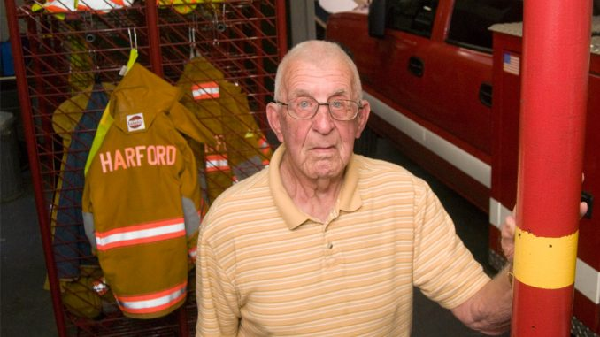 Pete Barber, 90, is shown at the Harford Fire Station last Thursday, where he is the last surviving founding member. He has been a member since playing a key role in the creation of the town's fire department in 1953.