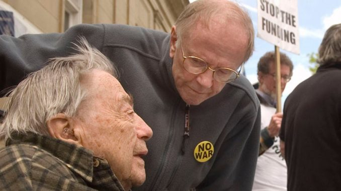Robert Rhodes leans in to chat with Dr. Edward Cummins during a 2008 protest against the conflict in Iraq in front of the post office in Cortland. Rhodes died Saturday at 89.