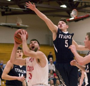 Bob Ellis/staff photographer Riley Thompson (5) of Ithaca leaps in an attempt to block a shot by Justin Cooper of SUNY Cortland on Tuesday.